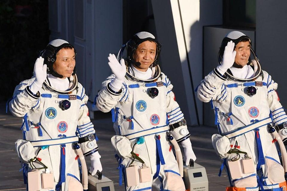 Astronauts Nie Haisheng (C), Liu Boming (R) and Tang Hongbo salute during a departure ceremony  (AFP via Getty Images)