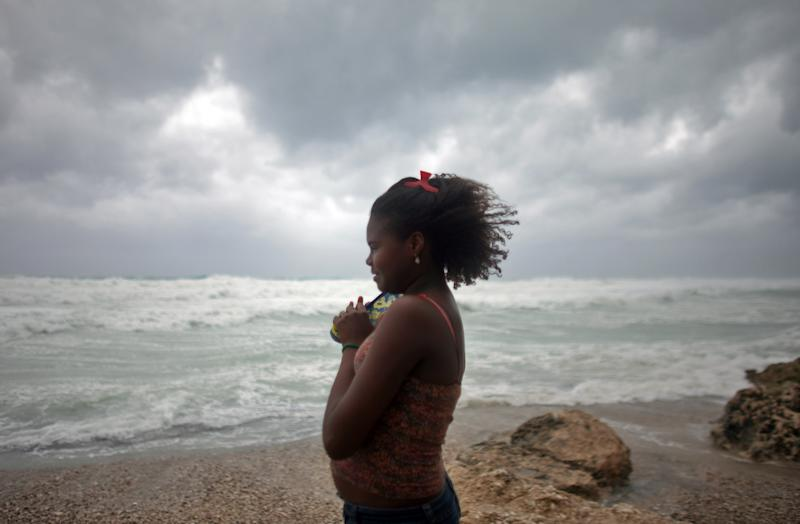 A woman looks out at the sea as Tropical Storm Isaac approaches Barahona, Dominican Republic, Friday, Aug. 24, 2012. Tropical Storm Isaac strengthened slightly as it spun toward the Dominican Republic and vulnerable Haiti on Friday, threatening to bring punishing rains but unlikely to gain enough steam to strike as a hurricane. (AP Photo/Ricardo Arduengo)