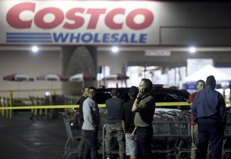 A Costco employee talks on the phone following a shooting within the wholesale outlet in Corona, Calif.,  Friday, June 14, 2019.  A gunman opened fire inside the store during an argument,  killing a man, wounding two other people and sparking a stampede of terrified shoppers before he was taken into custody, police said. The man involved in the argument was killed and two other people were wounded, Corona police Lt. Jeff Edwards said.  (Will Lester/Inland Valley Daily Bulletin/SCNG via AP)