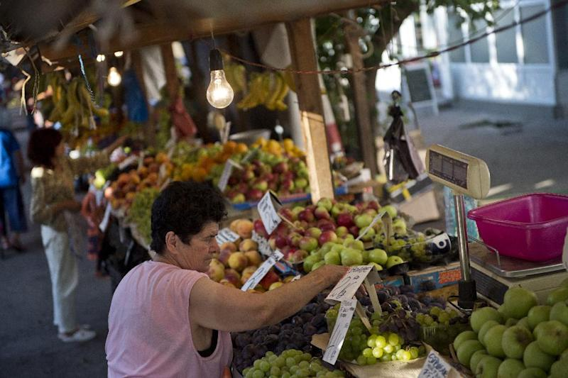 Vendors arrange their fruits and vegetables to be sold at a marketplace in Bucharest August 20, 2014