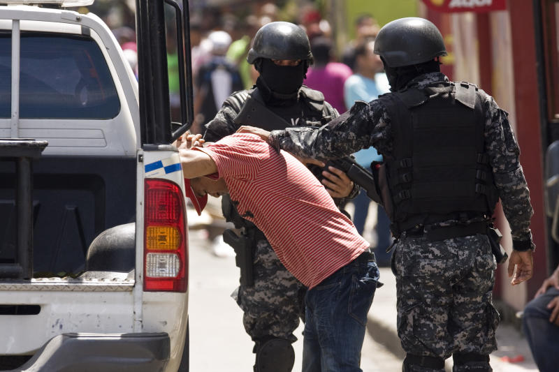 A police officer detain a man who they believed to be involved in the looting of stores in Panama City, where protesters battled police with sticks and rocks, and police fired tear gas, Friday, Oct. 26, 2012. Panama's government said Friday it will cancel plans to sell state-owned land in a duty-free zone following a week of sometimes violent protests in which a 10-year-old boy and two adults died. Though the land in question is in the port city of Colon, protests spread to Panama City. (AP Photo/Arnulfo Franco)