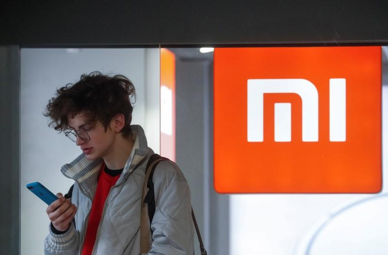 A man uses his smartphone next to the Xiaomi brand's store in central Kiev
