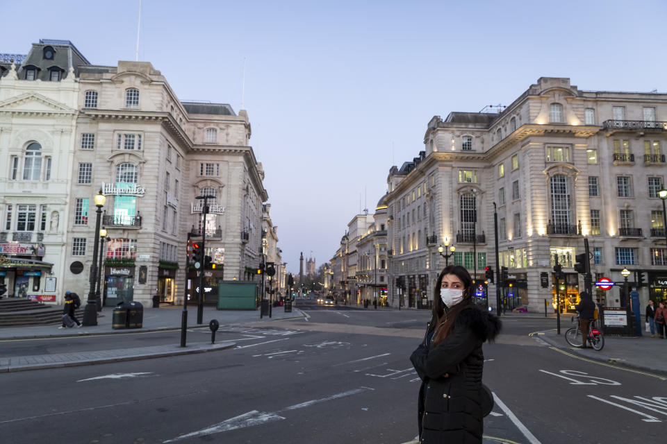 A woman wearing a face mask stands in an almost deserted Picadilly Circus in London on March 27th, 2020. The centre of London is extremely quiet with almost every business closed and very few people about because of the Government's lockdown measures due to the Coronavirus crisis. (Photo by Jonathan Perugia/In Pictures via Getty Images)