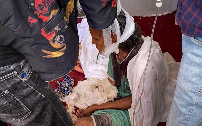 An elderly woman who fled from the town of Shire to the city of Axum to seek safety, but was then wounded in the jaw during an attack on the city - AP