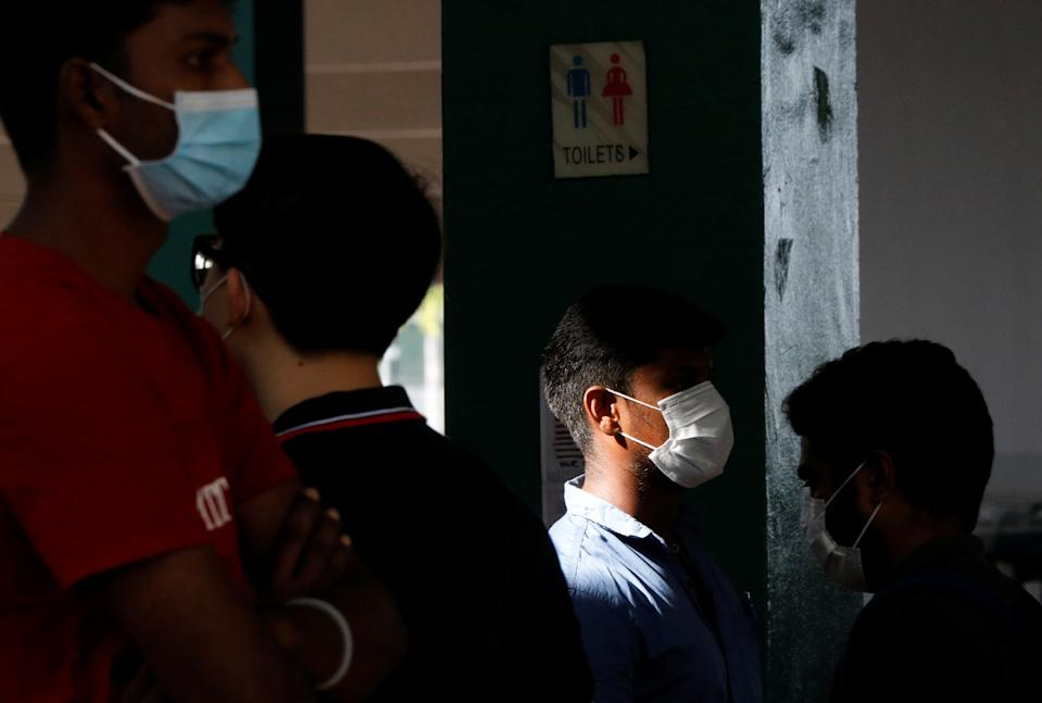 Essential workers queue up to have their noses swabbed before returning to the workforce at a regional screening centre amid the coronavirus disease outbreak in Singapore on 9 June, 2020. (PHOTO: Reuters)