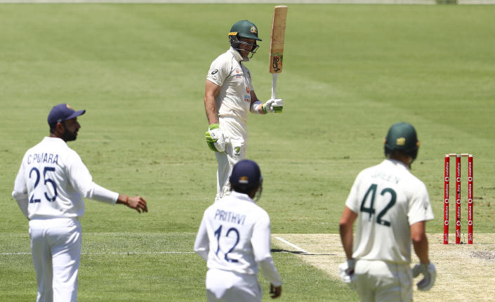 Australia's Tim Paine gestures with his bat on reaching 50 runs during play on day two of the fourth cricket test between India and Australia at the Gabba, Brisbane, Australia, Saturday, Jan. 16, 2021. (AP Photo/Tertius Pickard)