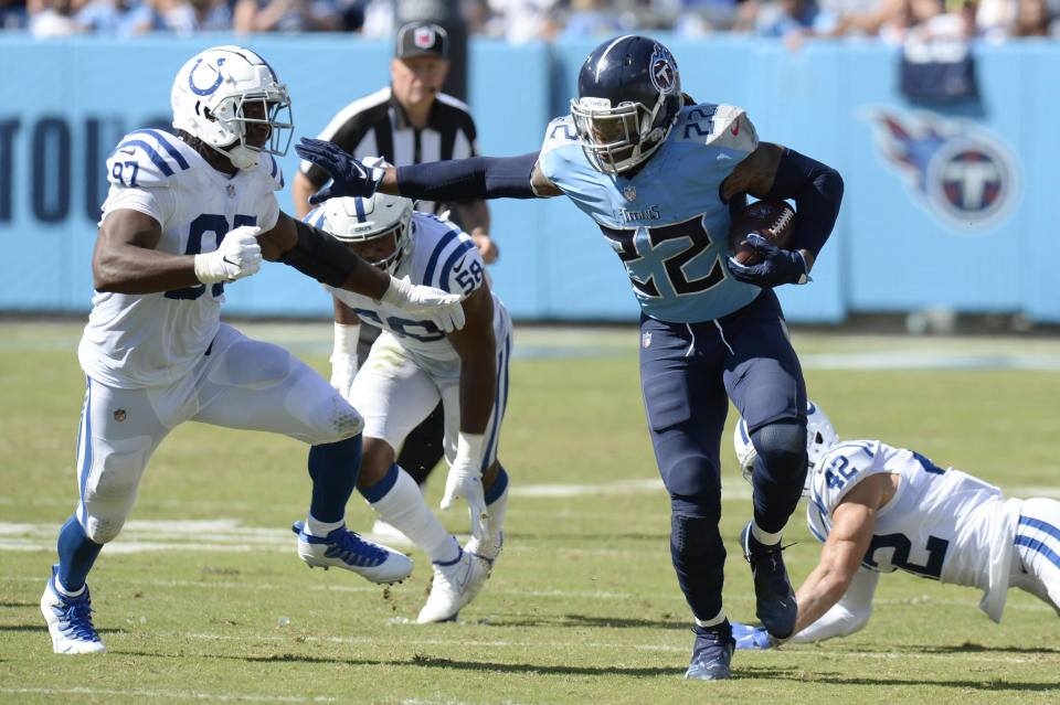 Tennessee Titans running back Derrick Henry (22) gets past Indianapolis Colts defensive tackle Al-Quadin Muhammad (97) and safety Andrew Sendejo (42) in the second half of an NFL football game Sunday, Sept. 26, 2021, in Nashville, Tenn. (AP Photo/Mark Zaleski)