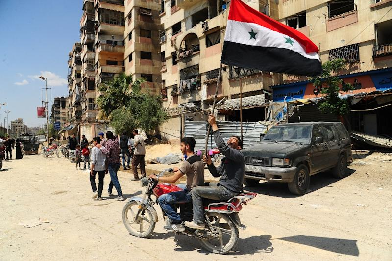 Men waive the Syrian flag on April 14, 2018 as they drive a motorcycle in a street in the Eastern Ghouta town of Douma after Syrian government forces retook the rebel bastion (AFP Photo/Handout)