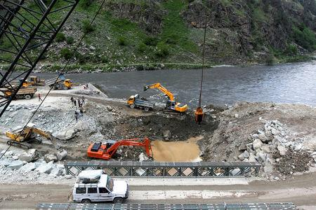 FILE PHOTO: A private vehicle crosses a bridge as excavators are used at the dam site of Kishanganga power project in Gurez, 160 km (99 miles) north of Srinagar June 21, 2012. REUTERS/Fayaz Kabli/File Photo