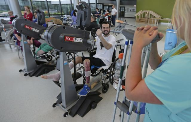 "In this Wednesday, May 22, 2013 photo, Boston Marathon bombing survivor Pete DiMartino, of Rochester, N.Y., smiles while talking with his therapist Julia Broyer during a session at the Spaulding Rehabilitation Hospital in Boston. DiMartino was injured in an explosion near the finish line, which blew away much of one leg and burned the other. ""I don't want anybody feeling sorry for me,"" he said. ""... I want people to see that this has made me a better person and I want people to become better people through what they see through me."" (AP Photo/Charles Krupa)"