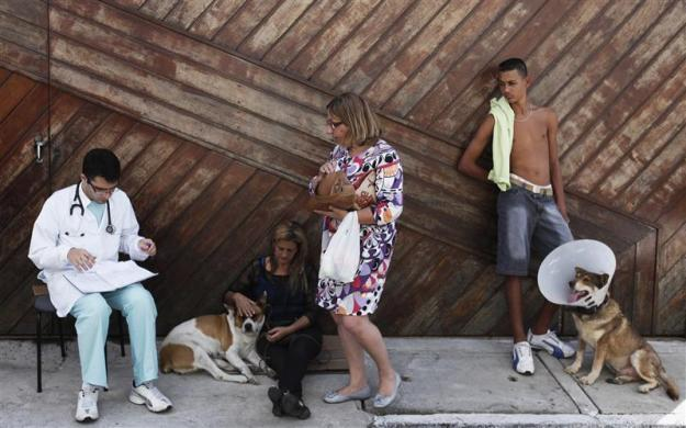 A veterinarian (L) talks with pet owners outside the Anclivepa-SP veterinarian hospital, financed by Sao Paulo's municipal government, which opened two months ago offering free health care for the pets of low-income residents, in Sao Paulo August 22, 2012. The city of Sao Paulo, home to three million domestic pets according to government statistics, opened Brazil's first public veterinary hospital in providing free care to cats and dogs belonging to poor families who are unable to pay for treatment.