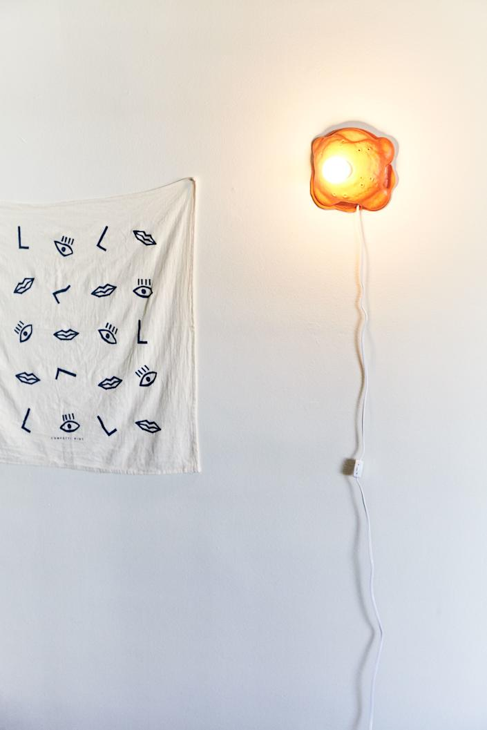 """This tapestry is actually a tea towel Leah bought on Etsy years ago, and next to it is Joseph Algieri's sconce for Clever x Urban Outfitters. """"I snatched that up the day it went on sale. I'm obsessed with his work,"""" she says of the sconce."""