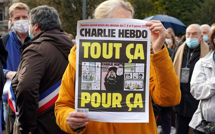"""A woman holds a sign saying: """"Charlie Hebdo. All for this"""" during the rally in memory of Samuel Paty in Lille - Sylvain Lefevre/Getty Images"""