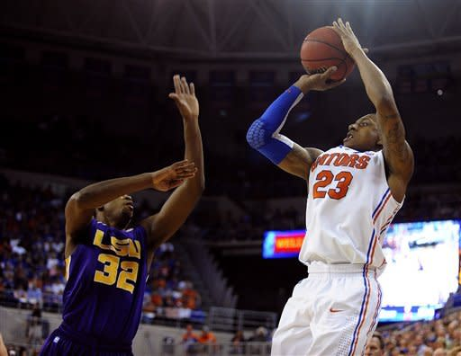 Florida's Bradley Beal (23) shoots for three points with LSU's John Issac (32) trying to block the shot, which was good, during the first half of an NCAA college basketball game in Gainesville, Fla., Saturday, Jan. 21, 2012. (AP Photo/Phil Sandlin)
