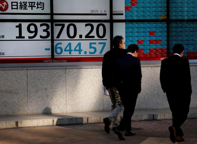 Men walk past an electronic board showing Nikkei average outside a brokerage in Tokyo, Japan, January 4, 2019. REUTERS/Kim Kyung-Hoon