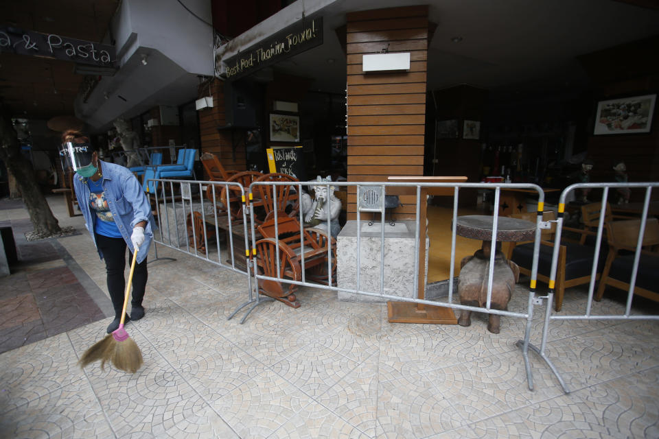 A worker wearing a face mask to help curb the spread of the coronavirus sweeps with a broom around a restaurant in Khao San road, a popular hangout for Thais and tourists in Bangkok, Thailand, Monday, April 26, 2021. Cinemas, parks and gyms were among venues closed in Bangkok as Thailand sees its worst surge of the pandemic. A shortage of hospital beds, along with a failure to secure adequate coronavirus vaccine supplies, have pushed the government into imposing the new restrictions. (AP Photo/Anuthep Cheysakron)