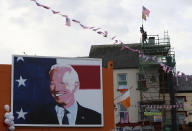 Men erect flags on top of a building as residents begin celebrations in the ancestral home of Joe Biden in anticipation of the results of the US election, in Ballina, Ireland, Saturday, Nov. 7, 2020. Biden was elected Saturday as the 46th president of the United States, defeating President Donald Trump in an election that played out against the backdrop of a pandemic, its economic fallout and a national reckoning on racism. (Brian Lawless/PA via AP)