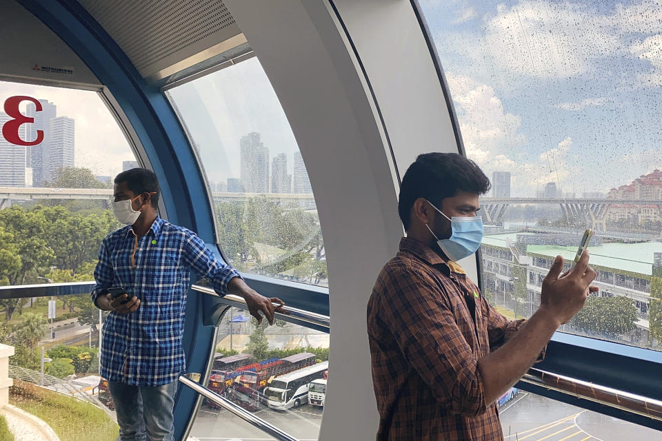Migrant workers on board the Singapore Flyer attraction in Singapore in March 2021. He is among at least 20,000 migrant workers who will be treated to rides by members of the public and businesses. Migrant workers are getting a bird's eye view of Singapore, with the public's help. (AP Photo/Annabelle Liang)