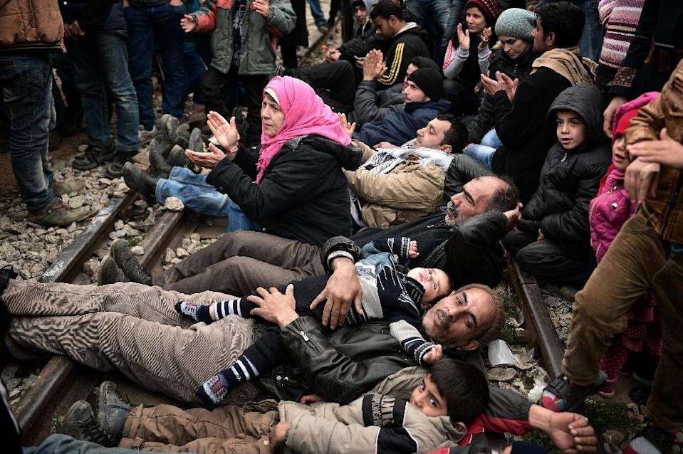 Syrian and Iraqi refugees trapped at the Greek-Macedonian border lie on railway tracks during a protest demanding the opening of the Idomeni crossing on February 28, 2016 (AFP Photo/Louisa Gouliamaki)
