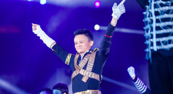 Alibaba cofounder Jack Ma raises his arms on stage at an event.