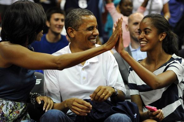 President Barack Obama shares a laugh with his wife Michelle and daughter Malia, as the US Senior Men's National Team and Brazil play during a pre-Olympic exhibition basketball game at the Verizon Center on July 16, 2012 in Washington, DC. (Photo by Patrick Smith/Getty Images)