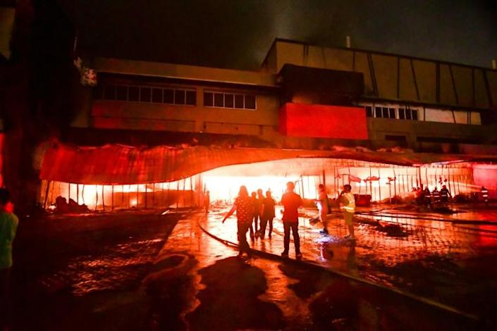The blaze at a shopping mall in General Santos City was still raging in the Philippines more than three hours after it began during an earthquake, despite the efforts of nearly 100 firemen, a fire officer said (AFP Photo/EDWIN ESPEJO)