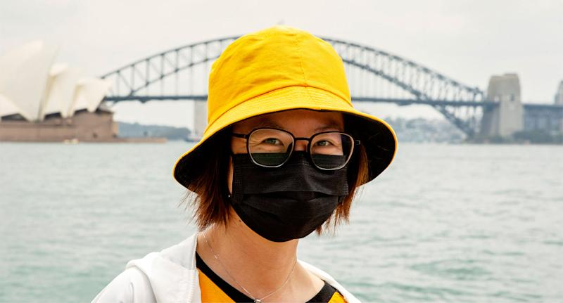 Woman in face mask standing before Sydney Opera House and the Harbour Bridge amid coronavirus.