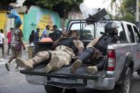 Police officers ride in the back of a pick-up truck with their weapons drawn during a protest to demand the resignation of Haiti's president Jovenel Moise on the 216th anniversary of Battle of Vertieres in Port-au-Prince, Haiti, Monday, Nov. 18, 2019. At least four people were shot and wounded during a small protest in Haiti's capital after a speech by embattled President Moise. A local journalist, a police officer and two protesters were rushed away with apparent bullet wounds. (AP Photo/Dieu Nalio Chery)
