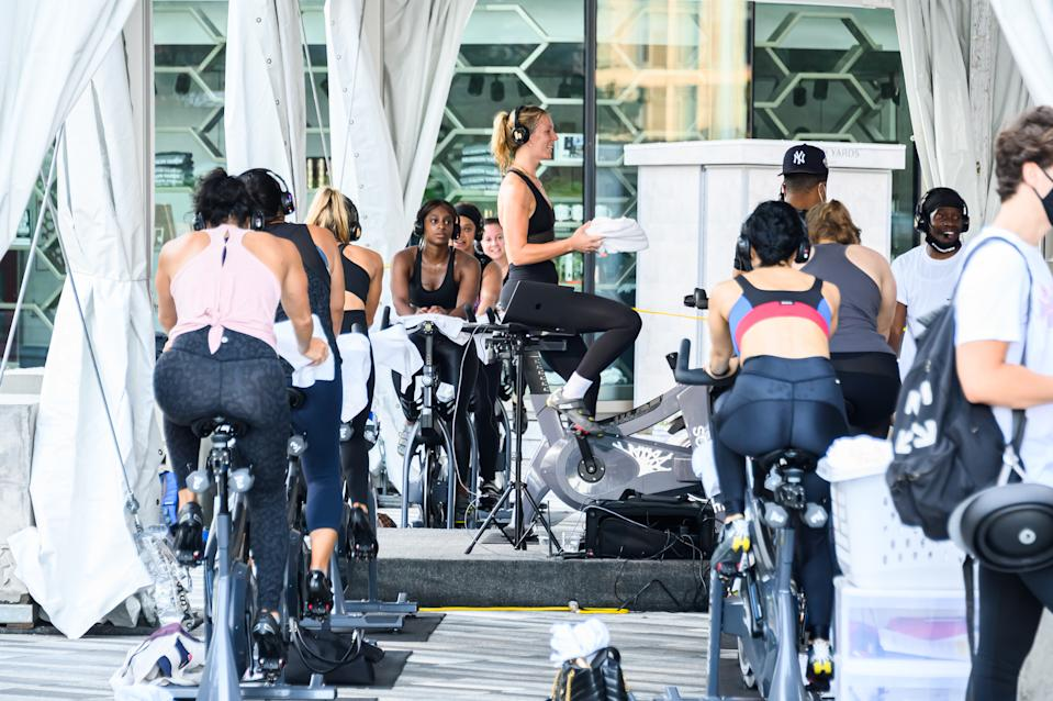 NEW YORK, NEW YORK - SEPTEMBER 04: People attend an outdoor SoulCycle class at the Hudson Yards as the city continues Phase 4 of re-opening following restrictions imposed to slow the spread of coronavirus on September 4, 2020 in New York City. The fourth phase allows outdoor arts and entertainment, sporting events without fans and media production. (Photo by Noam Galai/Getty Images)