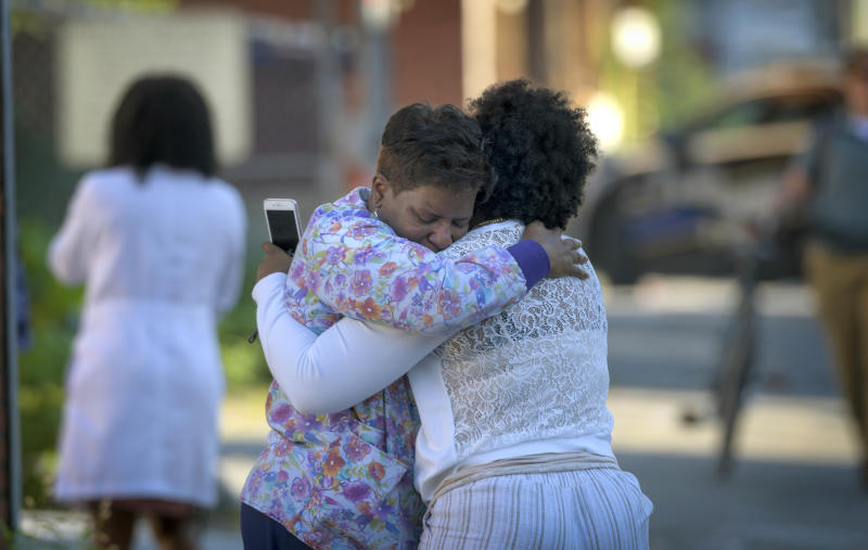 Two women embrace in an alley behind the Man Alive drug treatment center shortly after a shooting, Monday, July 15, 2019, in Baltimore. Two people are dead and a police sergeant and a woman are injured following a shooting at a methadone clinic in Baltimore, police said Monday.   (Jerry Jackson/The Baltimore Sun via AP)