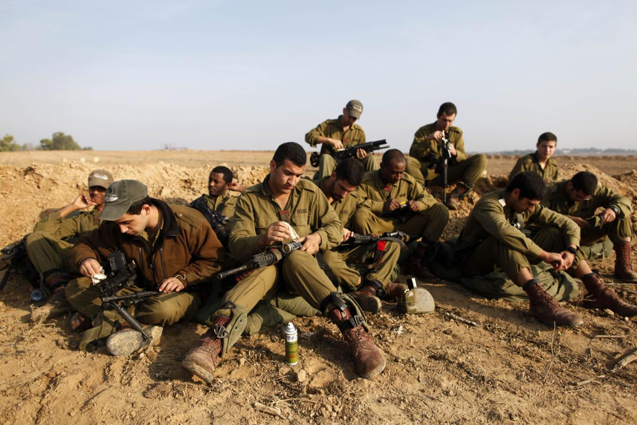 ISRAEL/GAZA BORDER, ISRAEL - NOVEMBER 19:  (ISRAEL OUT) Israeli soldiers prepare weapons in a deployment area on November 19, 2012 on Israel's border with the Gaza Strip. The death toll has risen to at least 85 killed in the air strikes, according to hospital officials, on day six since the launch of operation 'Pillar of Defence.'  (Photo by Lior Mizrahi/Getty Images)
