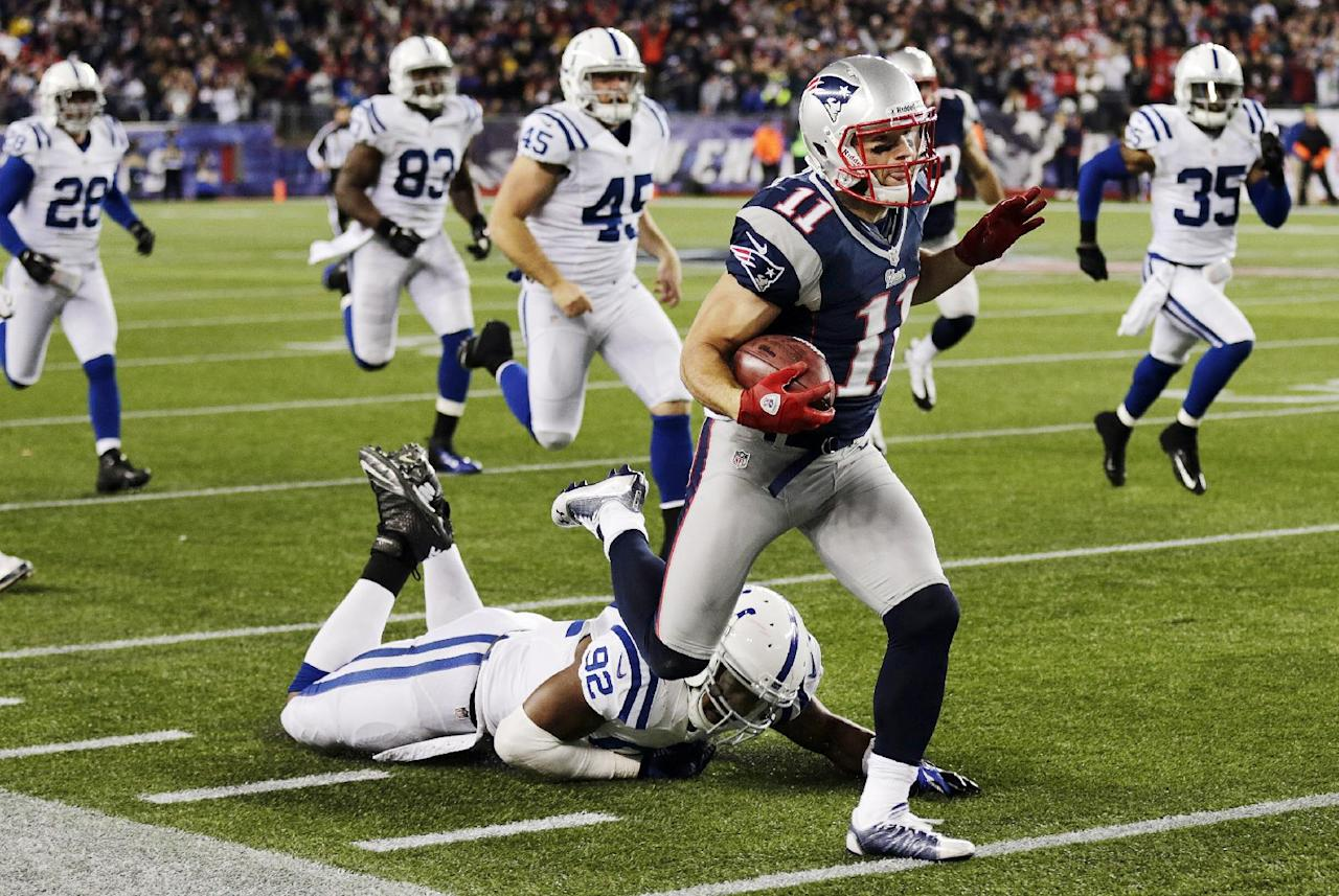 New England Patriots wide receiver Julian Edelman (11) eludes Indianapolis Colts outside linebacker Jerry Hughes (92) and other as he rushes for a touchdown in the second quarter of an NFL football game at Gillette Stadium in Foxborough, Mass., Sunday, Nov. 18, 2012. (AP Photo/Charles Krupa)