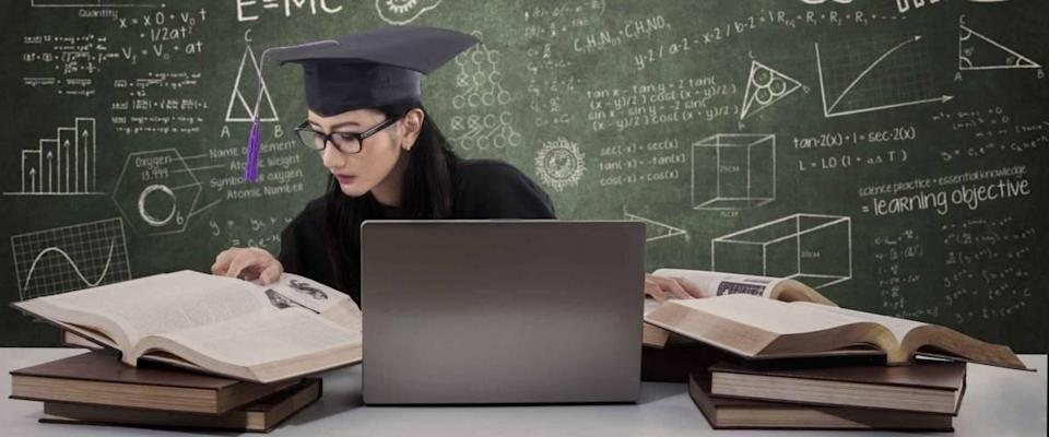 Busy female graduate doing her research with laptop in class
