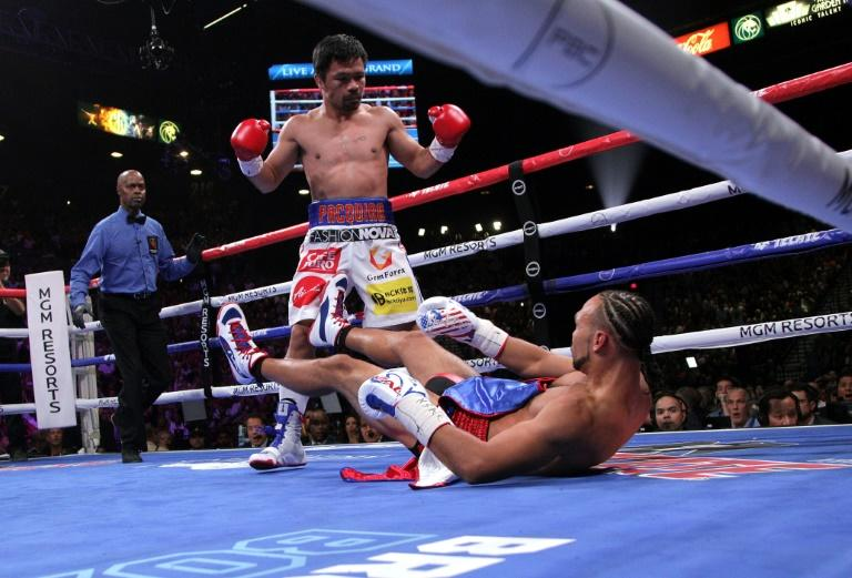 Manny Pacquiao sends Keith Thurman to the mat during the first round of their WBA super world welterweight title fight (AFP Photo/John Gurzinski)