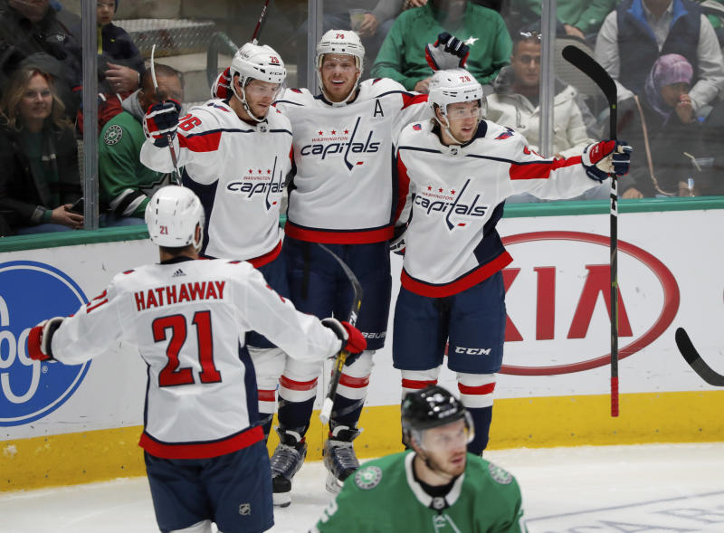 Washington Capitals' Garnet Hathaway (21), Nic Dowd (26), John Carlson (74) and Brendan Leipsic (28) celebrate a goal by Carlson as Dallas Stars defenseman Jamie Oleksiak, front, skates away in the second period of an NHL hockey game in Dallas, Saturday, Oct. 12, 2019. (AP Photo/Tony Gutierrez)