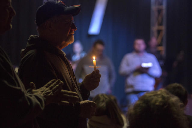 <p>Stan Collins of Benton, second from left, holds a candle during a vigil at Impact Church in Benton, Ky., Jan. 23, 2018. The vigil was held for victims of the Marshall County High School shooting earlier in the day. (Photo: Ryan Hermens/The Paducah Sun via AP) </p>