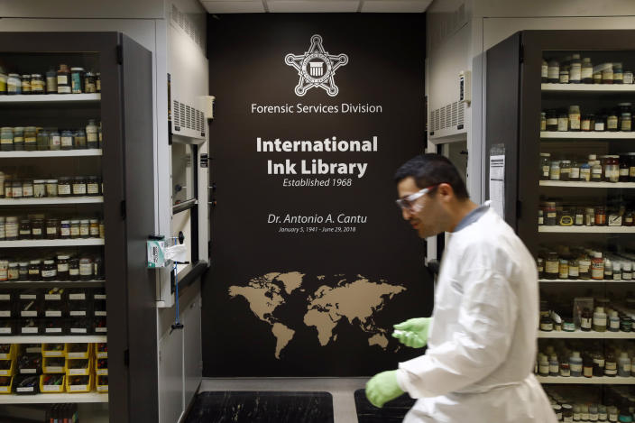 In this June 27, 2019 photo, document analysis technician Irvin Rivera carries an ink sample in the U.S. Secret Service's International Ink Library in Washington. The library was dedicated in remembrance of former chief chemist Antonio Cantu, who died suddenly last year. The library handles threat letters — the Secret Service protects not only the President but also other high-profile government officials — and phony documents, ransom letters and memorabilia. (AP Photo/Patrick Semansky)