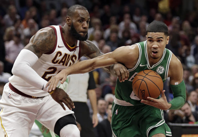 Boston Celtics' Jayson Tatum, right, drives past Cleveland Cavaliers' LeBron James in the first half of an NBA basketball game, Tuesday, Oct. 17, 2017, in Cleveland. (AP Photo/Tony Dejak)