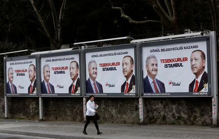 A woman walks past by AK Party billboards with pictures of Turkish President Tayyip Erdogan and mayoral candidate Binali Yildirim in Istanbul, Turkey, April 1, 2019.  REUTERS/Murad Sezer