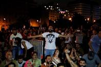 People gesture and chant slogans during a protest over deteriorating economic situation in Beirut