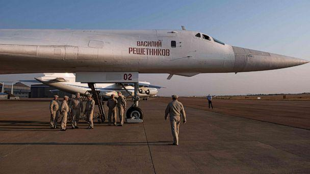 PHOTO: Military personnel gather under a Russian Air Force Tupolev Tu-160 'Blackjack' is parked on the tarmac at the Waterkloof Air force Base in Centurion, south of Pretoria, northeastern South Africa, on Oct. 23, 2019. (Emmanuel Croset/AFP via Getty Images)