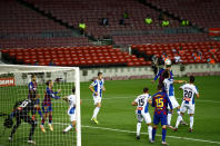 Barcelona's Gerard Pique jumps for the ball against Espanyol's Leandro Cabrera during the Spanish La Liga soccer match between FC Barcelona and RCD Espanyol at the Camp Nou stadium in Barcelona, Spain, Wednesday, July 8, 2020. (AP Photo/Joan Monfort)