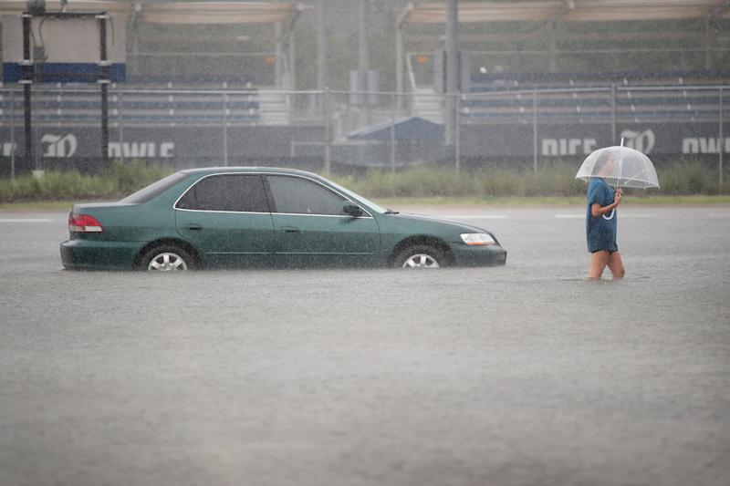 A woman walks through a flooded parking lot at Rice University in Houston last week.  (Scott Olson via Getty Images)