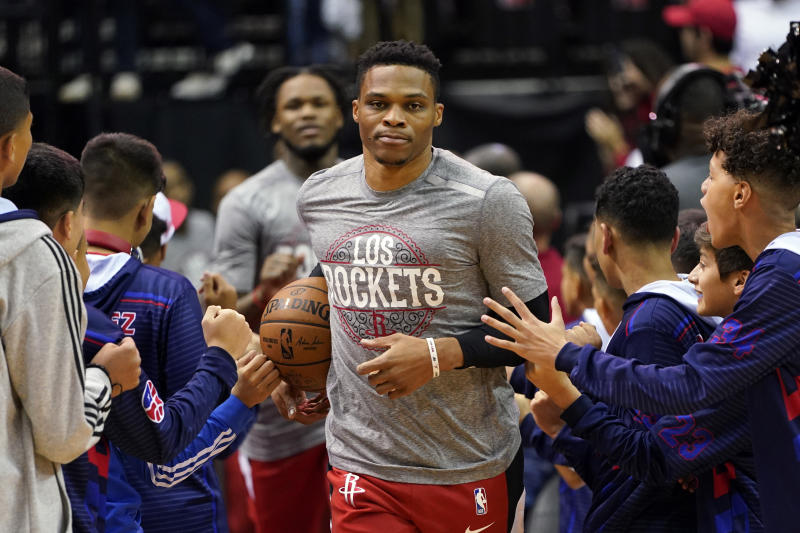 Houston Rockets' Russell Westbrook, center, enters the court as fans reach out before the Rockets' NBA basketball game against the Los Angeles Clippers on Thursday, March 5, 2020, in Houston. The NBA has told players to avoid high-fiving fans and strangers and avoid taking any item for autographs, the league's latest response in its ongoing monitoring of the coronavirus crisis. (AP Photo/David J. Phillip)