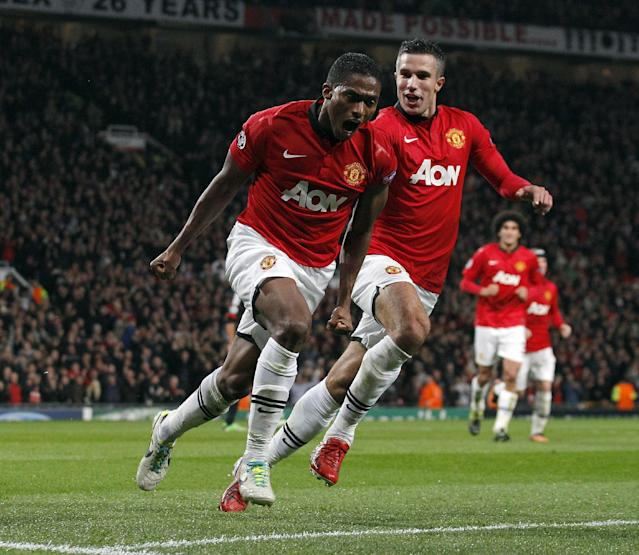 Manchester United's Antonio Valencia left, celebrates with team-mate Robin Van Persie after scoring the fourth goal of the game for his side during the Champions League Group A soccer match against Bayer Leverkusen, at Old Trafford in Manchester, England, Tuesday Sept 17, 2013. (AP Photo/Jon Super)