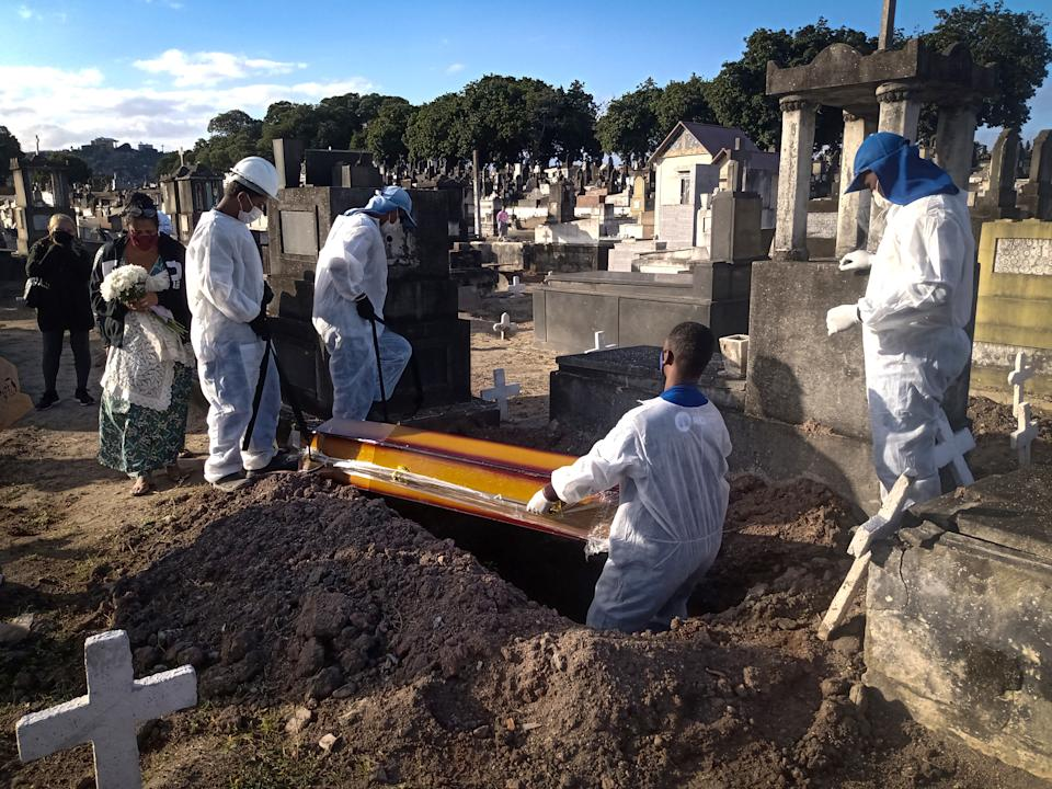 RIO DE JANEIRO, BRAZIL - JULY 29: Funeral workers carry out burials of Covid-19 victims at Inhauma Cemetery, north of the city, in Rio de Janeiro, Brazil on July 29, 2021. Brazil has more than 1,300 deaths for the 3rd day in a row this Thursday. The country reached the mark of 553,179 lives lost since the beginning of the pandemic. The number of infected is 19,839,369, with 42,283 new confirmed cases in the last 24 hours. (Photo by Fabio Teixeira/Anadolu Agency via Getty Images)