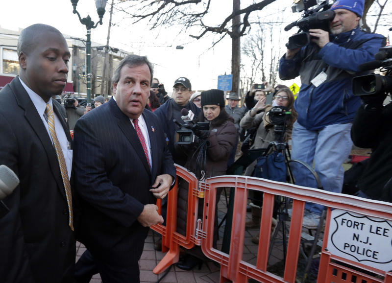 FILE - In this Jan. 9, 2014 file photo, New Jersey Gov. Chris Christie, second left, arrives at Fort Lee, N.J., City Hall. Christie traveled to Fort Lee to apologize in person to Mayor Mark Sokolich. Many people have known little about Fort Lee until a political scandal centering on Christie enveloped the borough. Now for residents of the New York City bedroom community defined by both a feisty pride and frustration over the mixed blessings of proximity to the George Washington Bridge, the scandal is the reminder they did not need of how the bridge dictates the rhythm of everyday life. (AP Photo/Richard Drew, File)