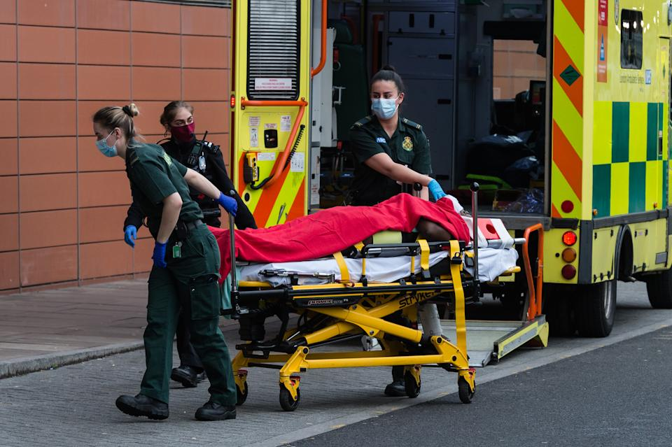 <p>Paramedics transport a patient from the ambulance to the emergency department at the the Royal London Hospital</p> (Getty)
