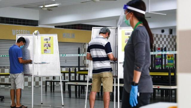 Election officials wore full protective gear and polling booths were sanitized every half hour. AP