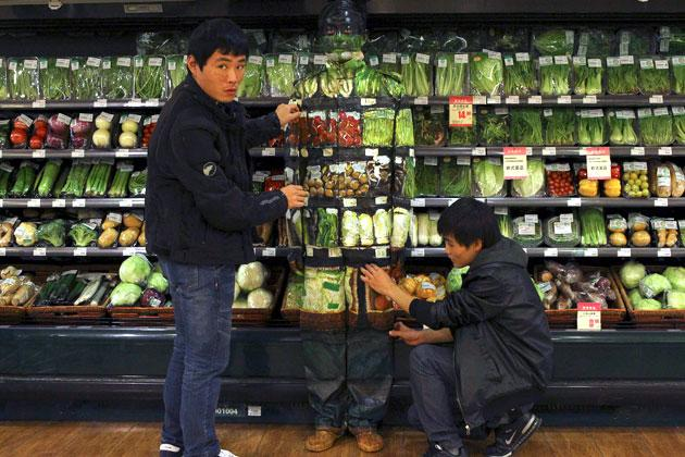 Assistants of artist Liu Bolin assist with his demonstration of blending in with the vegetables displayed on the shelves at a supermarket in Beijing, November 10, 2011. Liu, also known as the 'Vanishing Artist', started his optical illusion artworks of becoming 'invisible' more than six years ago. Picture taken November 10, 2011. REUTERS/China Daily